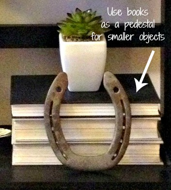 use books as a pedestal for smaller objects